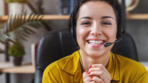 Happy young woman wear headset communicating by conference call speak looking at computer at home office