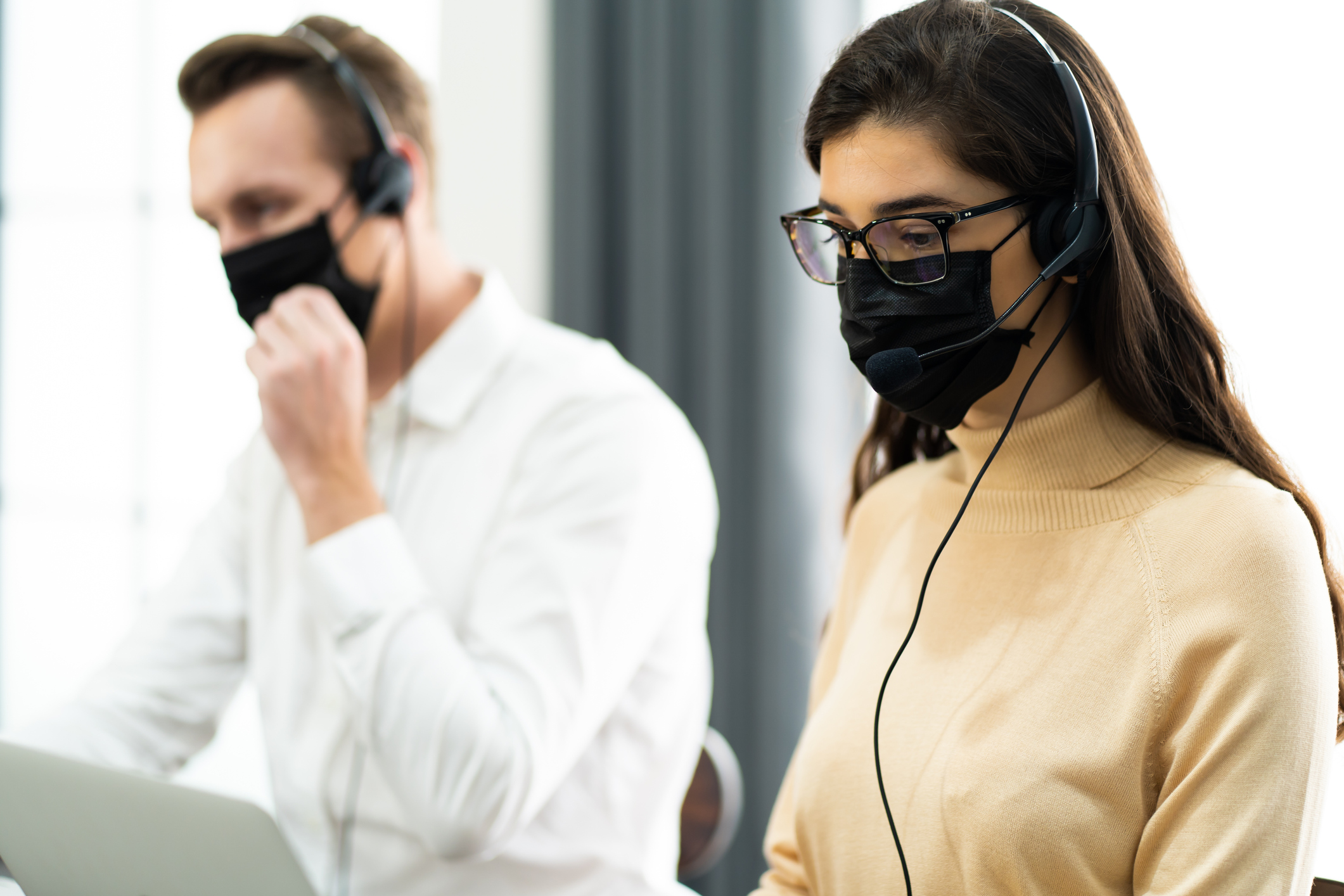 Beautiful female call center operator working on computer in office